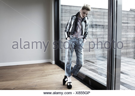 Young woman leaning against window, looking down - Stock Photo