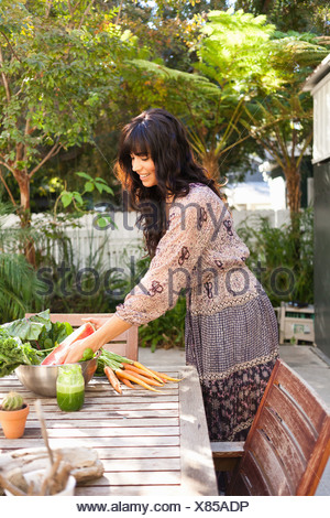 Young woman with vegetables on table - Stock Photo