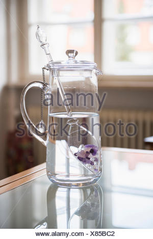 Water with gemstones in pitcher in kitchen - Stock Photo