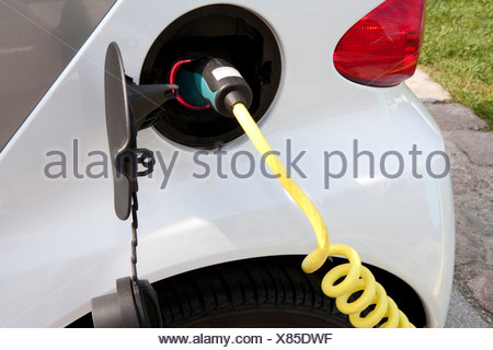 Detail of a charger connected to an electric car recharging - Stock Photo