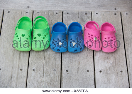 Childrens shoes on wooden decking - Stock Photo