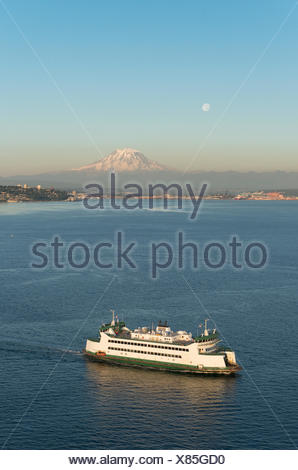 The Washington State Ferry sails in front of Mount Rainier and a full moon at sunset. - Stock Photo