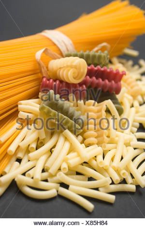 A bundle of spaghetti and various types of coloured pasta - - Stock Photo