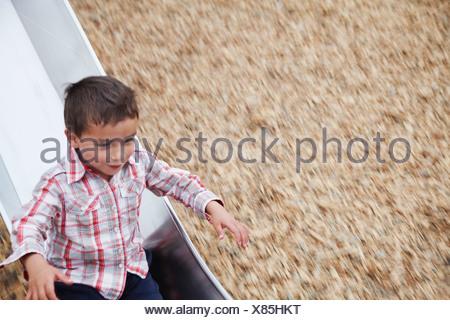 Boy playing on slide at playground - Stock Photo