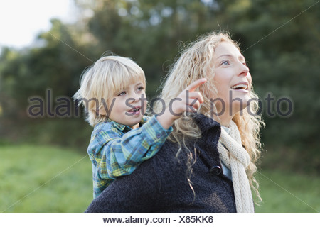 Mother carrying son piggyback outdoors - Stock Photo