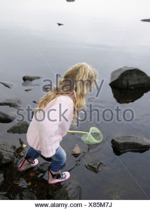 Young girl fishing in a lake with a net. - Stock Photo