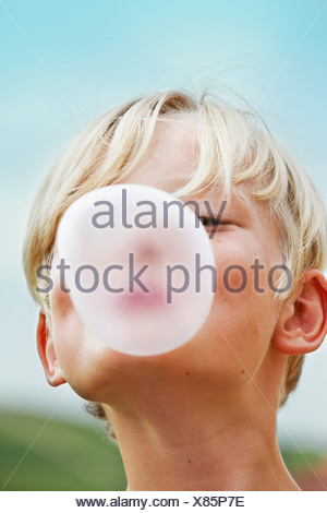 Smiling boy blowing bubble outdoors