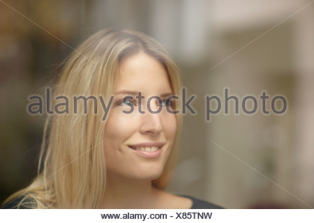 Woman smiling behind window - Stock Photo
