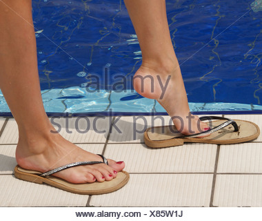 74e5f3179 ... young woman s feet with varnished toenails in flip-flops at the edge of  a swimming