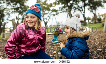 Two girls watching something on a playground in autumn - Stock Photo