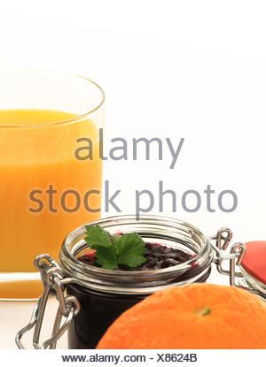 Ausschnitt eines Frühstückstisches mit Marmelade, Orangensaft und Orange - Stock Photo