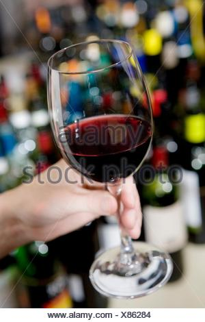Hand holding glass of red wine, wine bottles in background - Stock Photo