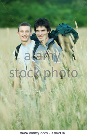 Two hikers standing in field, smiling at camera - Stock Photo