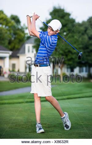 Teenage boy playing golf - Stock Photo