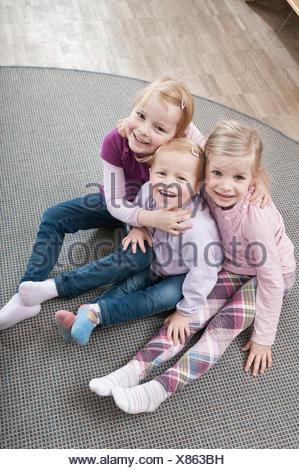 Three little girls, best friends, sitting on ground in kindergarten, elevated view - Stock Photo