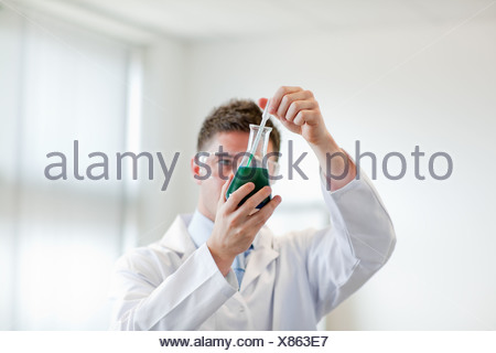 Handsome man in lapcoat looking at chemicals - Stock Photo