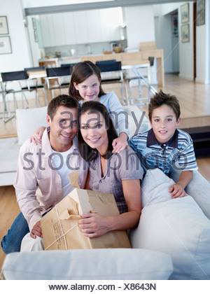 Man and woman with boy and girl sitting on sofa with package - Stock Photo