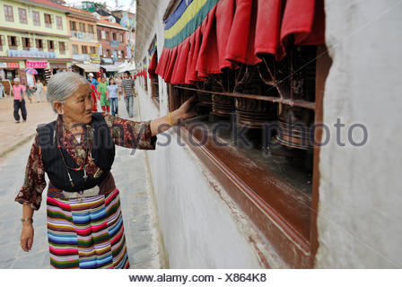 Pilgrim walking around stupa of Boudhanath and turning prayer wheel, Kathmandu, Nepal, Asia - Stock Photo