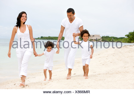 happy family, mum and dad with their two kids on holidays, walking along a beach - Stock Photo