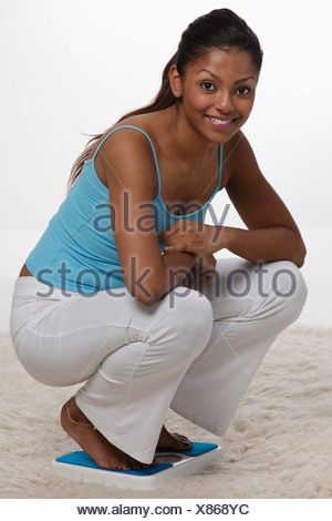 woman squatting on scale and smiling - Stock Photo