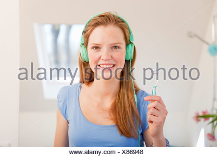 Teenage girl brushing her teeth - Stock Photo