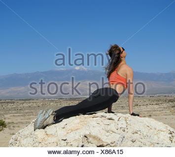 Woman doing an upward facing dog yoga pose on a rock in the desert, Nevada, America, USA - Stock Photo