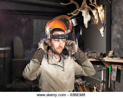 Blacksmith putting on a visor in workshop - Stock Photo