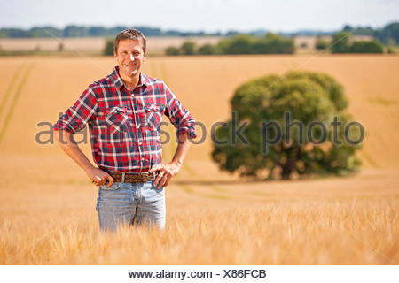 Portrait confident farmer with hands on hips in sunny rural barley crop field - Stock Photo