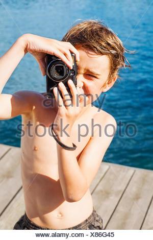 Sweden, Uppland, Runmaro, Barrskar, Portrait of boy (6-7) photographing on jetty - Stock Photo