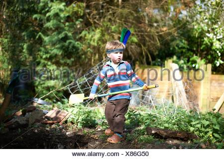 Young boy wearing headband with feathers, holding spade - Stock Photo