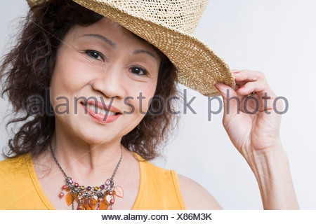 Portrait of a senior woman holding her hat - Stock Photo