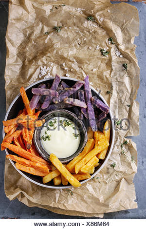 Variety of french fries traditional potatoes, purple potato, carrot served with white cheese sauce, salt, thyme in bowl on baking paper gray metal bac - Stock Photo