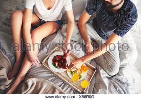 Couple relaxing on bed, eating strawberries, elevated view - Stock Photo