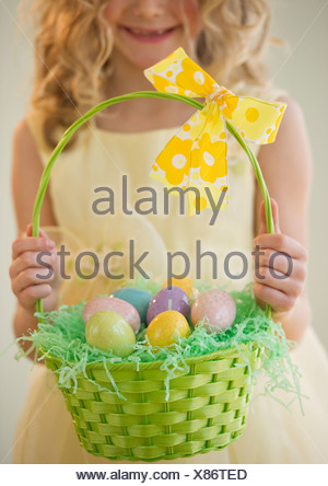 Young girl holding a basket of Easter eggs - Stock Photo
