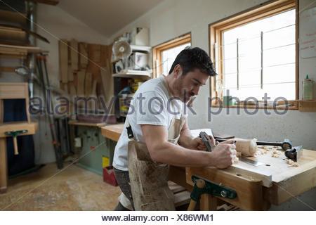 Carpenter working in workshop - Stock Photo