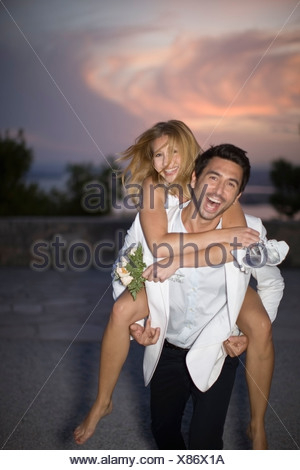 Man carrying his bride - Stock Photo