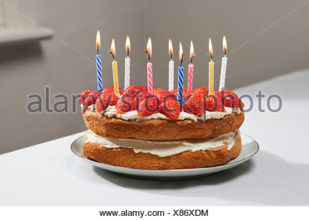Lit candles on birthday cake - Stock Photo