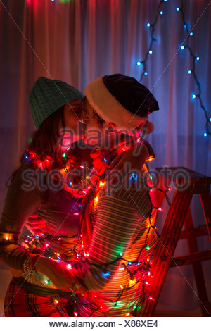 Young couple wrapped in fairy lights at christmas - Stock Photo