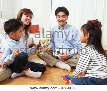 A small girl playing xylophone while family members look at her - Stock Photo