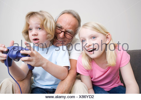 Grandfather and grandchildren (8-9) playing video game, portrait - Stock Photo