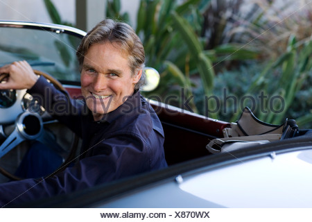 Man sitting in convertible car smiling over his shoulder - Stock Photo
