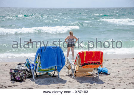 Empty chairs, with bags and towels, and a woman in the distance at the beach. - Stock Photo