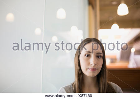 Portrait serious businesswoman leaning on frosted glass - Stock Photo