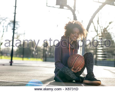 Portrait of smiling young woman with basketball sitting on a playing field - Stock Photo