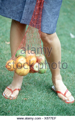1801cc64f083d Cropped female wearing denim skirt and red flip flops walking in ...