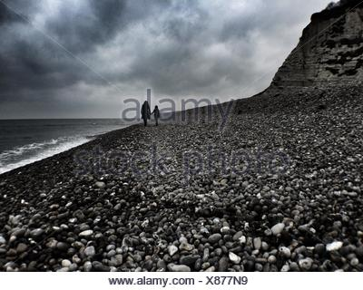 Silhouette Of Mother And Daughter Walking At Beach Coastline - Stock Photo