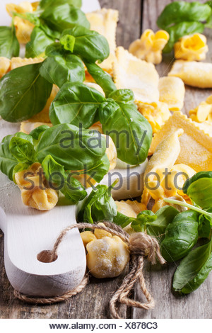 Homemade pasta ravioli and perle on old wooden table with fresh basil. - Stock Photo