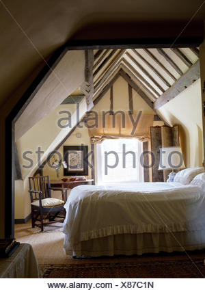 White linen on bed in country bedroom with beamed apex ceiling - Stock Photo