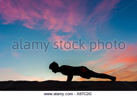 Side view silhouette of mid adult man doing push up against dramatic sky - Stock Photo