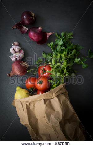 Vegetables in paper bag fresh from the market on slate background: Top view - Stock Photo